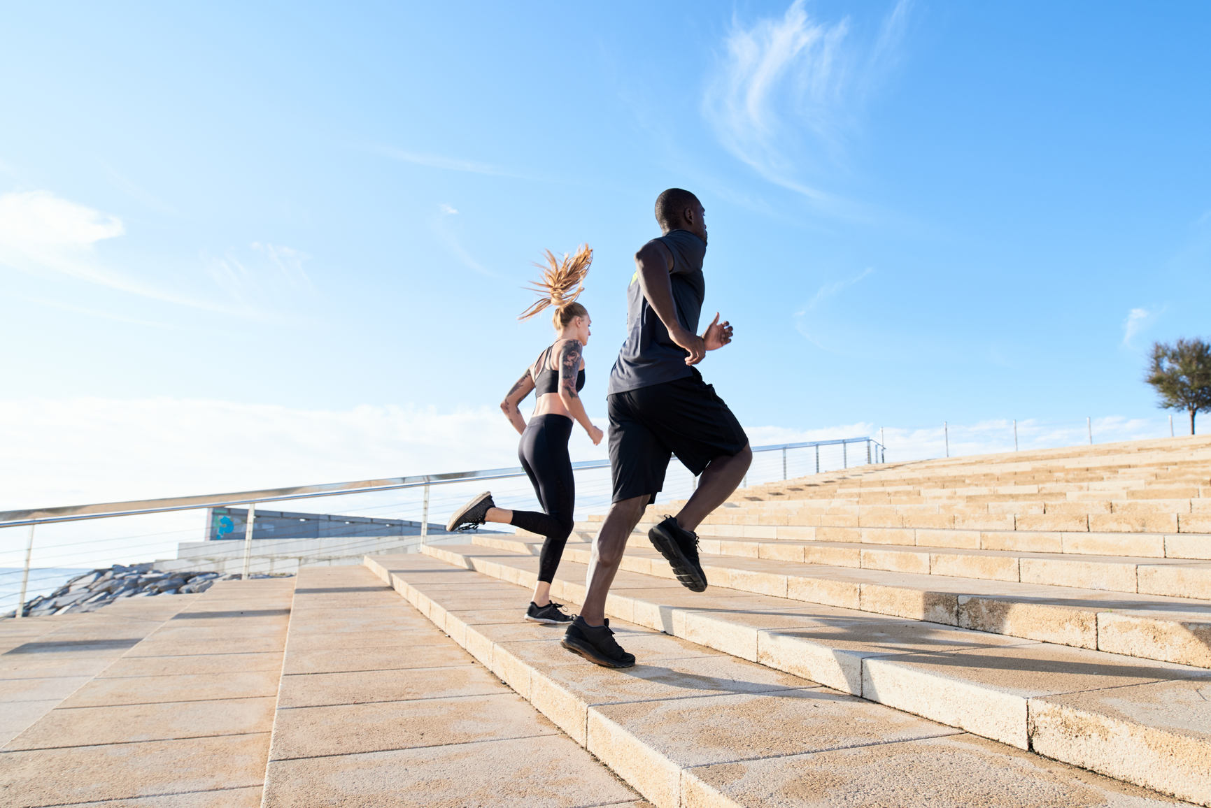 Two young people training together in seafront running up stairs in morning time.