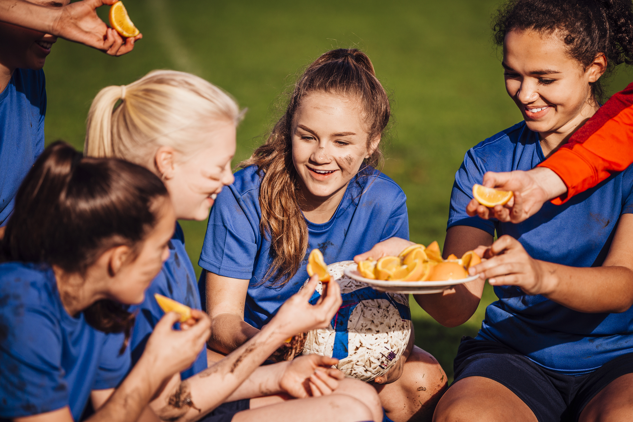 Young teenage girls sitting down to eat some fresh sliced oranges. Dirty sitting with a soccer ball and all smiling