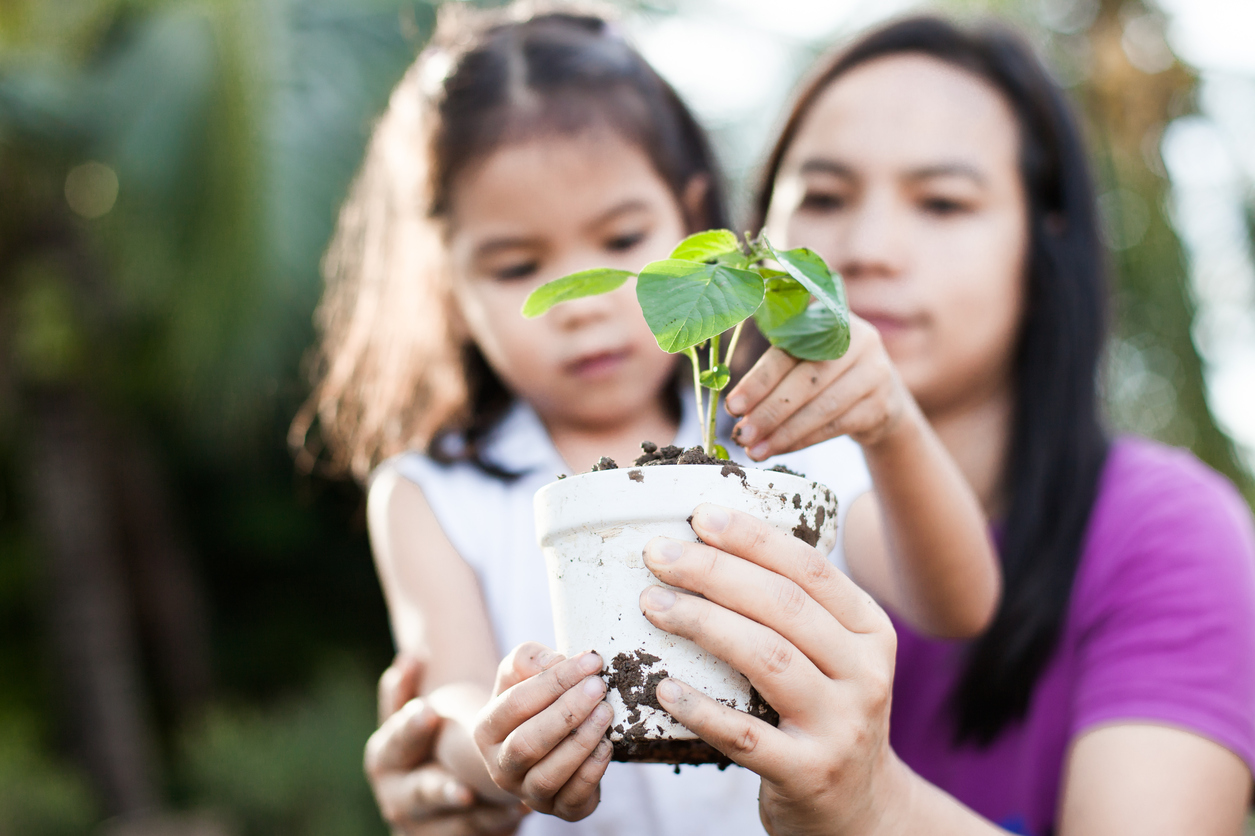 Cute asian little child girl and parent holding young tree in pot together for prepare plant on ground as save world concept in vintage color tone