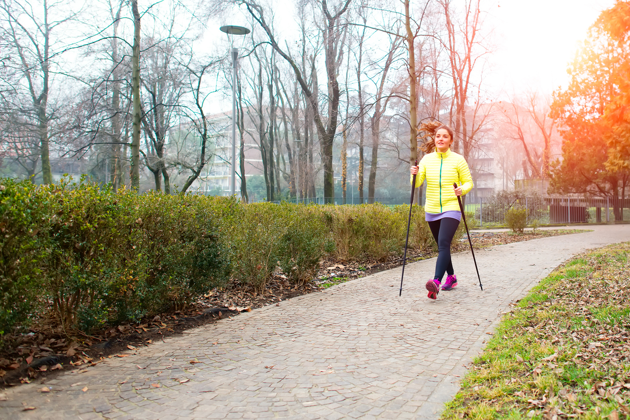 Girl make Nordic walking in the park in the city
