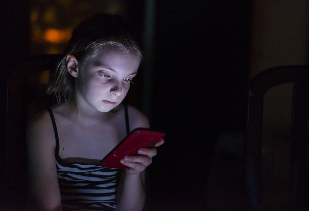 Teenager checks her mobile phone in bed during the night. technology, internet, communication and people concept - close up of teen girl texting on smartphone at home at night.  Internet Addiction Disorder