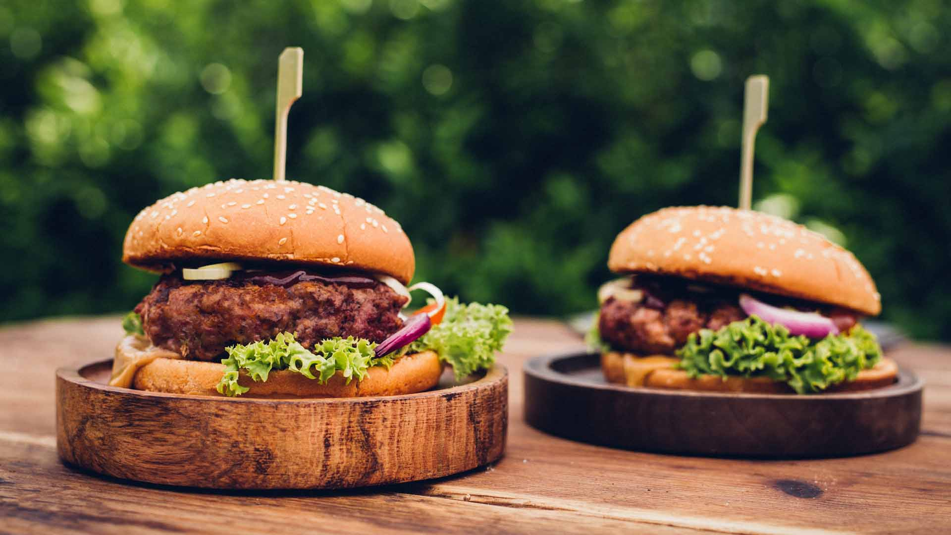 Two delicious gourmet beef burgers on wooden platters outdoors