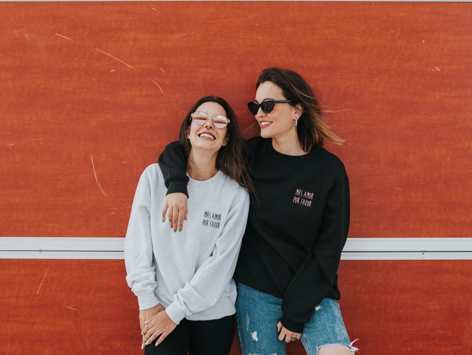 Portrait of two women with sweatshirt and sunglasses on the beach