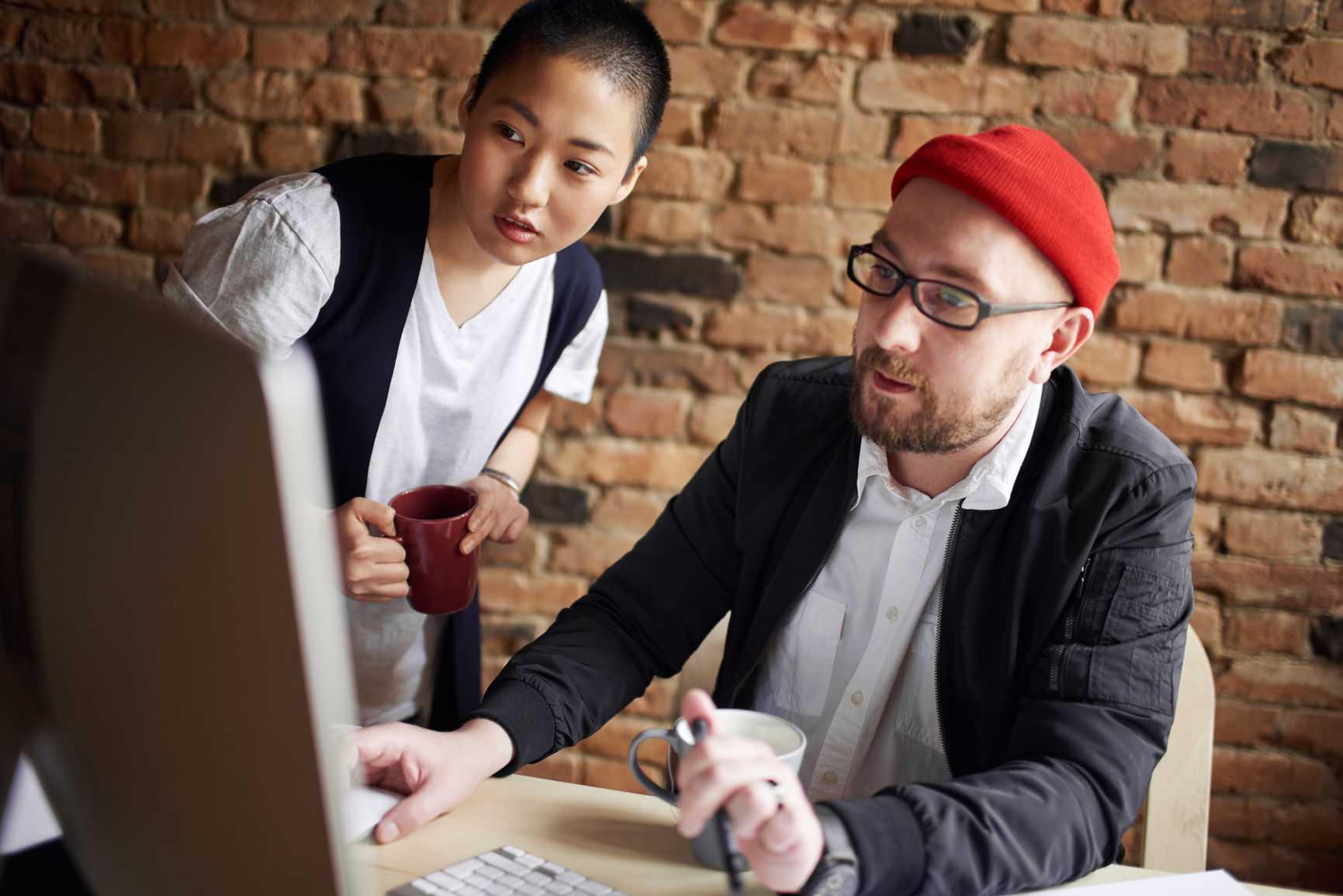 Male art director and his enthusiastic female coworker looking at computer screen attentively against brick wall background