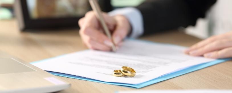 Closeup of woman signing papers at a desk, rings lying on paperwork