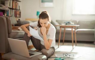 A woman sitting in front of a laptop holding a piece of paper