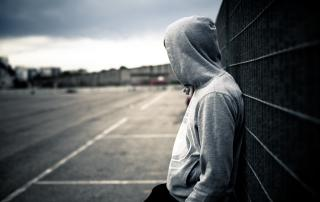 Youth wearing hoodie looking away into distance