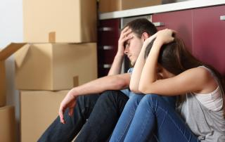 Couple sitting on floor, boxes piled behind, looking forlorn