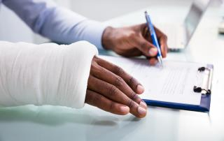 Person with bandaged arm signing a document