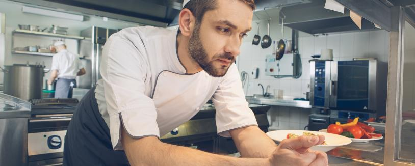 Kitchen worker with arms resting on counter, looking concerned