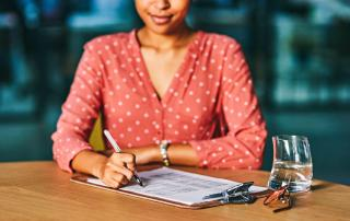 Woman at table signing paperwork attached to a clipboard