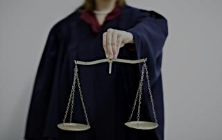 Person in robes holding scales of justice
