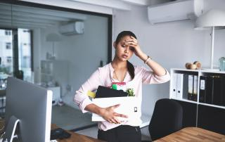 Woman in office holding files and placing hand to forehead