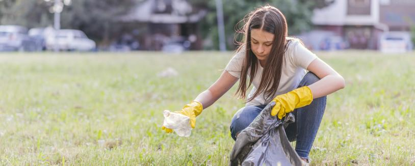 Young woman picking up trash from the ground in field