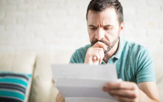 Bearded man looking pensive, looking at piece of paper