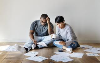 Couple on floor of empty room, looking at paperwork