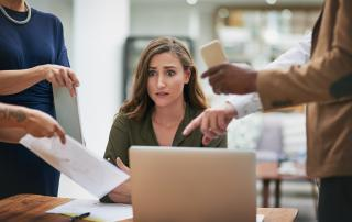 Woman looking concerned as colleagues point to paper