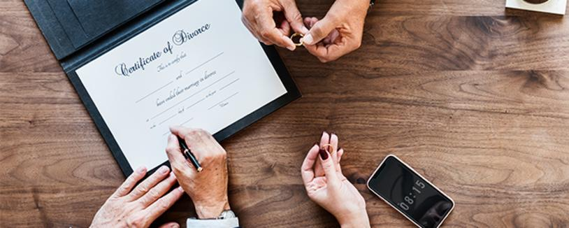 Couple holding wedding rings with certificate of divorce on the table