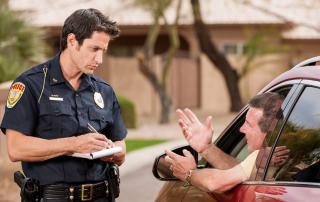 Police officer giving man a traffic ticket