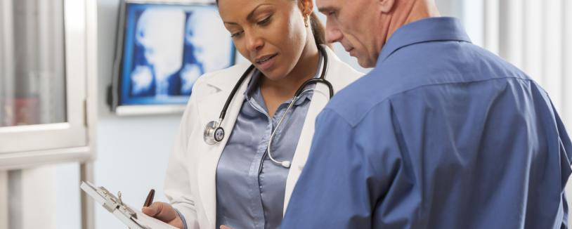 A doctor holding a clipboard talks with a patient