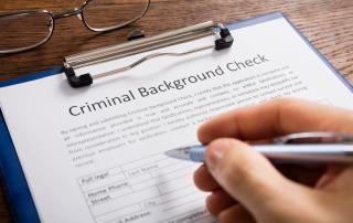 Clipboard with criminal background check and person filling it out