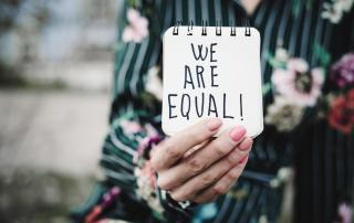 Person holding up notepad with 'We are equal!' written on it
