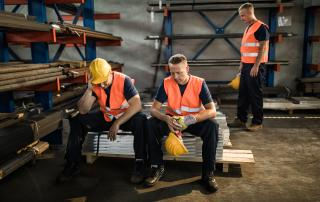 Two men in warehouse, sitting on stack of building supplies
