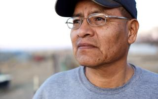 Indigenous man with glasses and ball cap looking Into distance