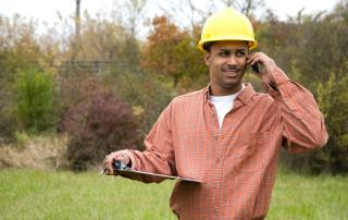Man in field holding clipboard and talking on phone