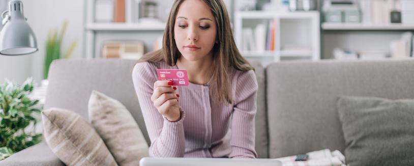 Young woman looking a back of credit card