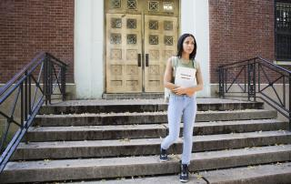 Woman walking down steps, holding student loan application