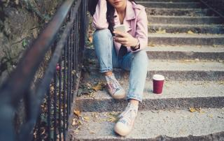 Young person sitting on steps outside holding a phone