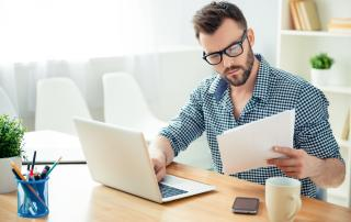 Man in glasses with laptop reading paperwork