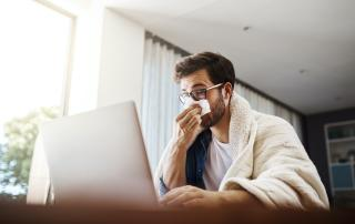 Man holding tissue to his nose, on laptop