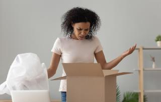 Woman opening a box looking unhappy