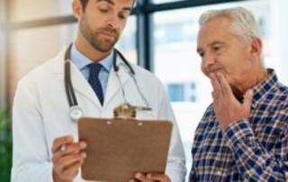 A doctor shows a clipboard to an older man