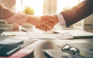 Two people shaking hands across a table