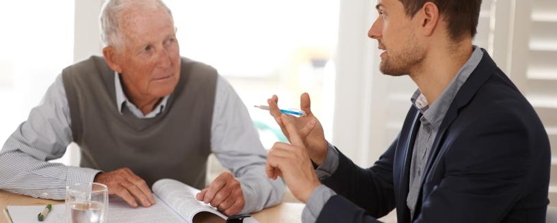 An older man consulting with an advisor, sitting at table