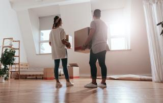 Couple moving boxes into empty room