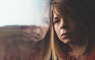 Woman looking out the window with subdued expression