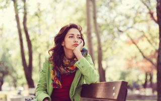 A young woman outside on park bench looking into the distance