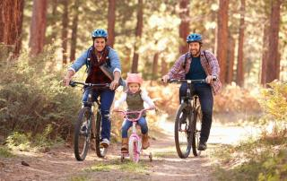 Couple with daughter cycling along forest path