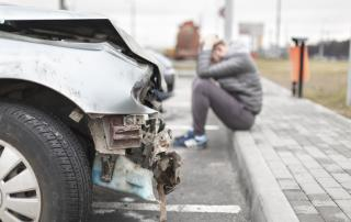Front bumper of car damaged with man sitting on the sidewalk holding his head after having been in an accident