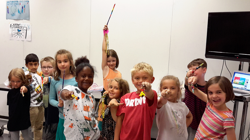 A group of campers holding wands.