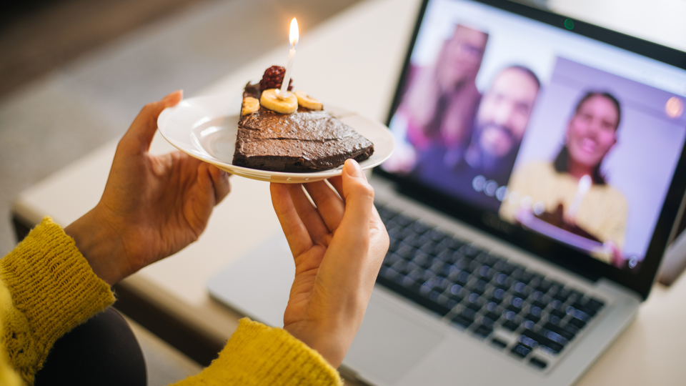 A person holding a slice of birthday cake while chatting with other people through their laptop.