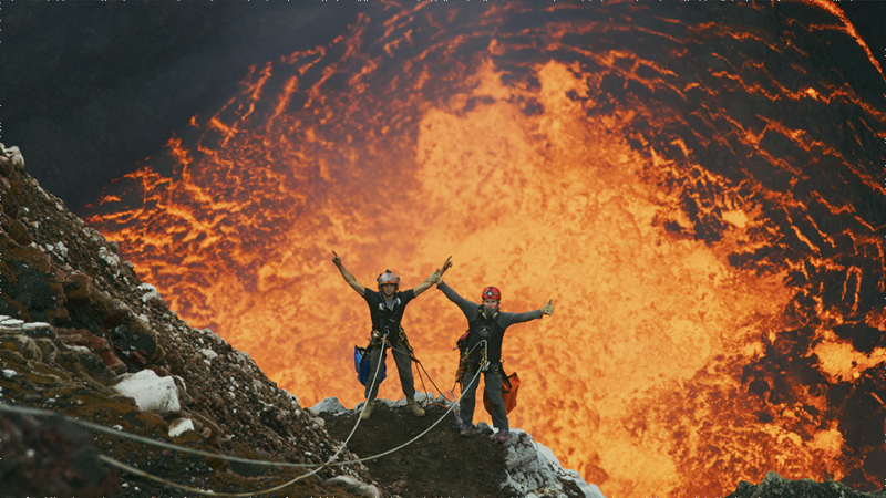 Two people exploring the inside of a Volcano.