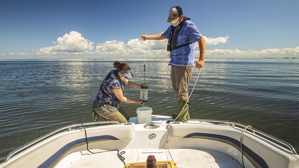 Science Museum of Minnesota scientists Adam Heathcote and Alaina Fedie collecting water samples.
