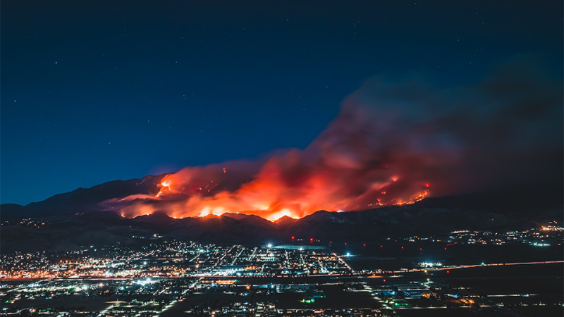 Fires burning nearby a city in California at night.