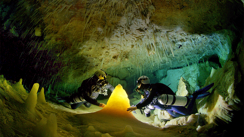 Two people exploring an underwater cave in scuba-diving outfits.