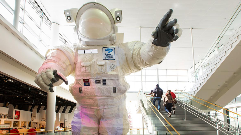 Image of the giant astronaut at the Science Museum with a family walking up the stairs nearby